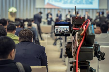 Closeup Video recording the Speaker with formal suit on the stage over Rear view of Audience in the conference hall or seminar meeting, event and seminar concept