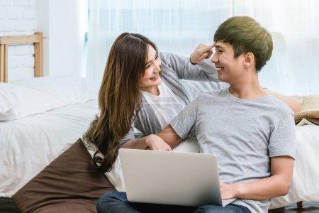 Nahaufnahme glückliche asiatische Liebhaber oder Paare, die miteinander reden und lächeln, wenn sie den Technologie-Laptop auf dem Bett im Schlafzimmer eines modernen Hauses verwenden, junge Frauen, die auf die Stirn des Freundes, Liebhabers und Lebensstilkonzepts zeigen,