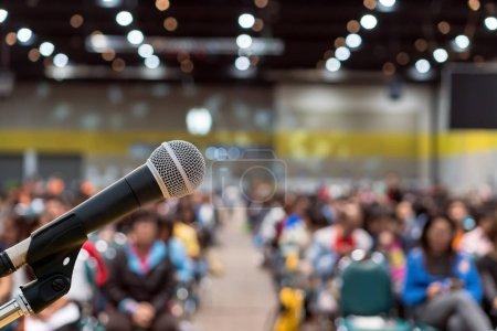 Photo for Microphone over the Abstract blurred photo of conference hall or seminar room in Exhibition Center background with Speakers on the stage and attendee background, Business meeting and education concept - Royalty Free Image