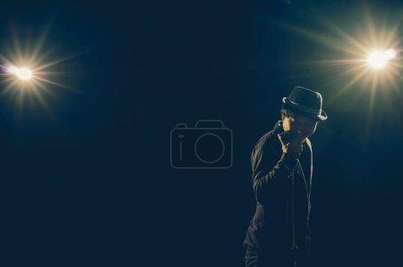 Photo pour Musicien asiatique chantant une chanson avec microphone sur fond noir avec projecteur et fusée éclairante, concept musical - image libre de droit