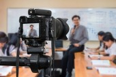 Professional digital Mirrorless camera on the tripod recording video blog of Asian teacher in the classroom,Camera for photographer or Video and Technology Live Streaming concept,University education