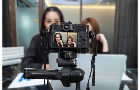 Professional digital Mirrorless camera with microphone recording video blog of two asian young businesswomen, Camera for photographer or Video and Live Streaming concept
