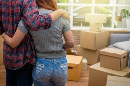 Photo for Back side of Asian young couple hugging together over the big cardboard box and sofa when moving in new house, Moving and House Hunting concept - Royalty Free Image