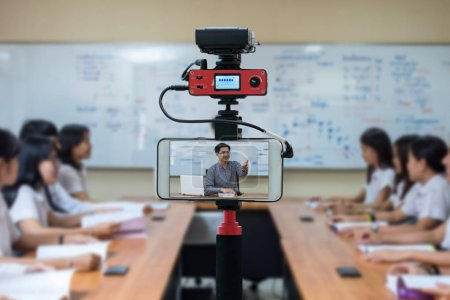 Closeup smart mobile phone taking Live of Asian teacher in the classroom,Camera for photographer or Video and Technology Live Streaming concept,University education