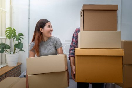 Asian young couple carrying big cardboard box for moving in new house, Moving and House Hunting concept