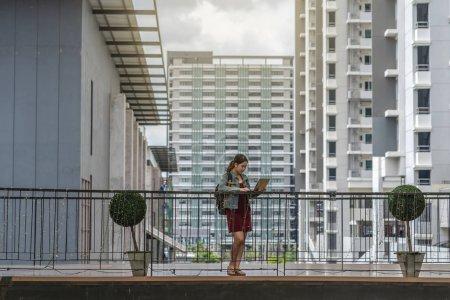 Photo pour Femme d'affaires asiatique avec le vêtement occasionnel restant et travaillant avec l'ordinateur portatif autour de l'extérieur du bureau ou du lieu de travail moderne dans la ville - image libre de droit