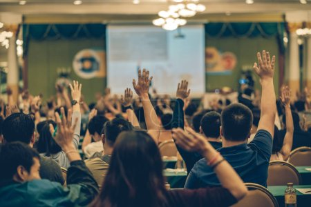 Photo for Rear view of Audience showing hand to answer the question from Speaker on the stage in the conference hall or seminar meeting, business and education concept - Royalty Free Image