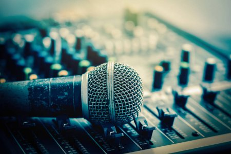 Closeup microphone over the audio mixer, vintage film style, music equipment concept