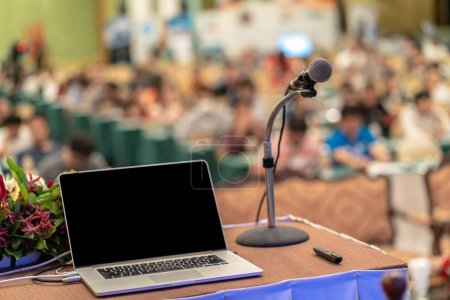 Microphone and tecgnology laptopn on the table over the Abstract blurred photo of conference hall or seminar room with audience background, education and learning concept