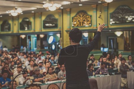 Rear view of Asian Speaker with casual suit standing and giving the knowledge over the photo blurred of audience in the conference hall or seminar meeting, business and education concept