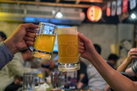 Two Glasses of Beer cheers together between friend in the bar and restaurant. relax and drink concept