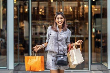 Photo for Happy Asian woman walking out from the department store and holding the shopping bag in downtown, fashion concept - Royalty Free Image