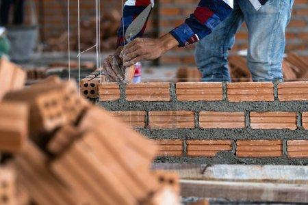 Photo pour Gros plan main travailleur de la construction professionnelle pose de briques dans le nouveau site industriel. construire l'industrie et la maçonnerie concept - image libre de droit