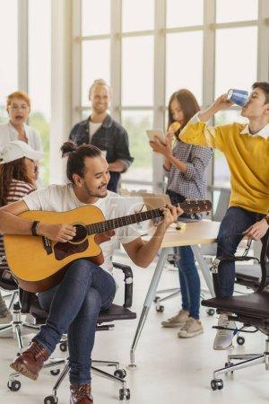 Photo for Asian worker playing the guitar over the Group Of Asian and Multiethnic Business people with casual suit talking and eatting with happy action when lunch time in the creative office workplace, life style and relax work concept - Royalty Free Image