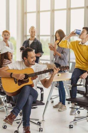 Photo pour Ouvrier asiatique jouant la guitare au-dessus du groupe des gens asiatiques et multiethniques d'affaires avec le costume occasionnel parlant et mangeant avec l'action heureuse quand l'heure de déjeuner dans le lieu de travail de bureau créateur, le modèle de vie et le concept de travail de détente - image libre de droit