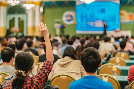 Foto de Vista posterior de la audiencia mostrando la mano para responder a la pregunta del orador en el escenario en la sala de conferencias o reunión de seminario, concepto de negocio y la educación - Imagen libre de derechos