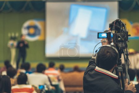 Photo for Rear side of Video Cameraman taking photograph to Asian Speaker with casual suit on the stage present the screen in the conference hall or seminar meeting, event and seminar production concept - Royalty Free Image