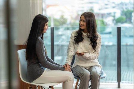 Photo pour Médecin professionnel asiatique de psychologue de femme donnant la consultation aux patients féminins dans le salon moderne de la maison ou de la salle d'examen d'hôpital, concept de santé mentale - image libre de droit