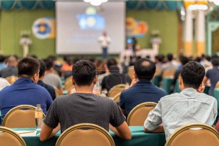 Photo pour Vue arrière du public à l'écoute des enceintes présentent la diapositive sur la scène dans la salle de conférence ou de réunion séminaire, de concept d'affaires et l'éducation - image libre de droit