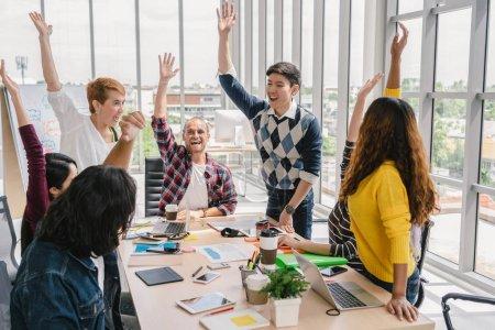 Foto de Grupo de empresarios asiáticos y multiétnicos con un traje casual de pie y coordinación de la mano con acción feliz para el trabajo en equipo en el lugar de trabajo moderno, concepto de grupo empresarial de personas - Imagen libre de derechos