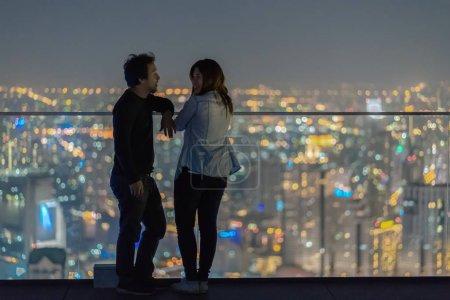 Foto de Pareja romántica de pie en la azotea desde bangkok edificio moderno por la noche sobre la foto borrosa de fondo del paisaje urbano, amante y el concepto de vacaciones calentinas, poca luz - Imagen libre de derechos