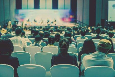 Photo pour Vue arrière du public écoute interviennent sur la scène du hall ou séminaire réunion, le commerce et la formation sur le concept d'investissement - image libre de droit