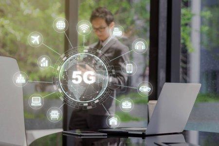 Photo pour Technologie 5G avec divers icône internet des choses sur ordinateur portable de la technologie et tablette avec tasse de café en papier sur l'espace de travail dans le bureau moderne avec un homme d'affaires asiatique debout et en utilisant mobile - image libre de droit