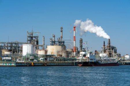 Photo pour Scène de la zone industrielle de raffinerie de pétrole à côté de la rivière sur l'heure de travail qui ont fumée de vapeur, usine et industrie avec concept de pollution - image libre de droit