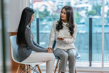 Photo for Asian woman professional psychologist doctor giving the consult to female patients in modern living room of house or hospital exam room, Mental health Concept - Royalty Free Image