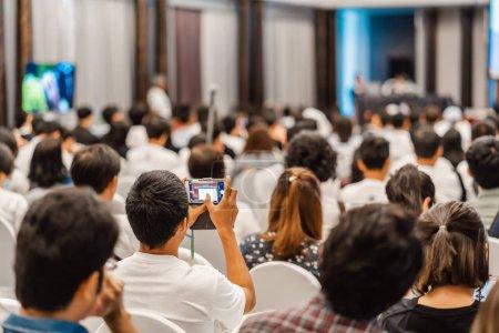 Photo pour Vue arrière de l'écoute du public Conférenciers et utilisation du téléphone portable pour prendre la photo dans la salle de conférence ou le séminaire réunion et atelier événement, affaires et éducation sur le concept d'investissement - image libre de droit
