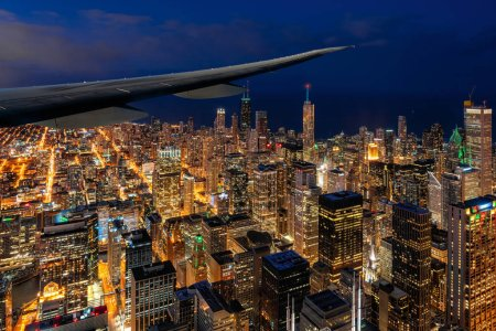 Photo for Airplane wing over the Aerial view of Chicago cityscape skyscraper under the blue sky at beautiful twilight time in Chicago, Illinois, United States, Landscape and Modern Architecture concept - Royalty Free Image