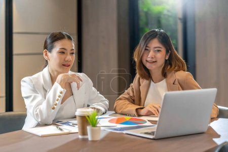 Photo for Two asian businesswomen working with the partner business via technology laptop in modern meeting room, office or working space, coffee break, partner and colleague concept - Royalty Free Image