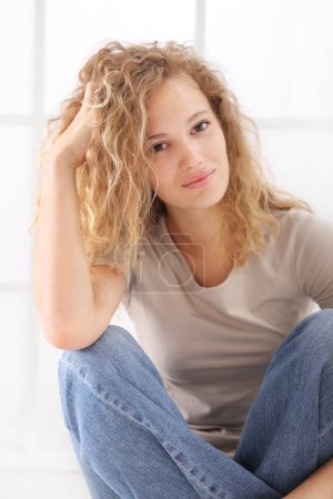portrait of young woman caressing her long hair, sitting on floor dressed in jeans and T shirt, isolared on white
