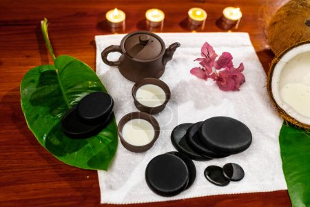 Photo pour A terry towel with a clay teapot and cups for drinks with milk, stones for stone therapy, candles, and a mannolia flower - image libre de droit