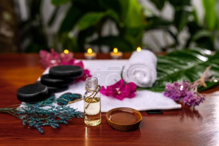 Photo pour A bottle with aromatic oil, a cup with poured oil located in front of a terry towel on which are stones for therapy stone, pink flowers and dried sprigs of lavender - image libre de droit