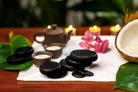 Photo pour A terry towel on which there is a clay teapot and cups for drinks with milk, stones for stone therapy, lighted candles, a mangolia flower and a twisted terry towel on a wooden table - image libre de droit