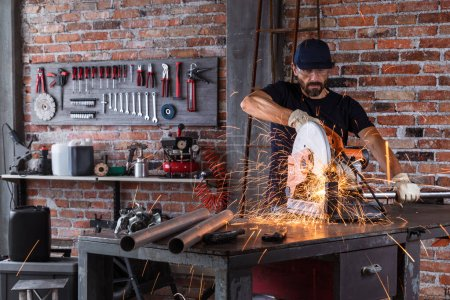 Photo for Man doing metalwork in a workshop using a grinding wheel with flying fiery sparks against a backdrop of tools - Royalty Free Image