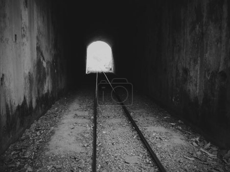 A gray scale shot of an old railway going through ...