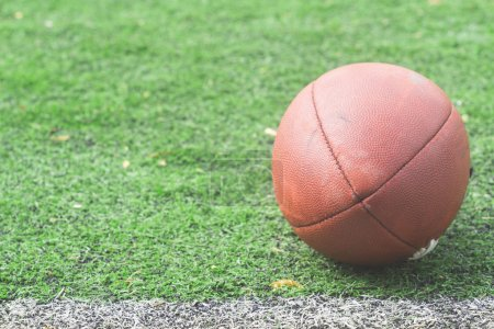 Leather football ball lying on green field