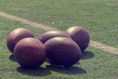 Pile of leather football balls on lying on green field