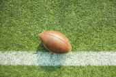 American football ball on the field with line.