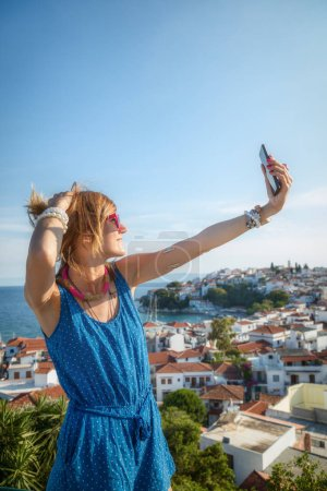 Girl making selfie with small sea town in the background.