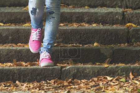 Female feet in pink sneakers while walking, close up view