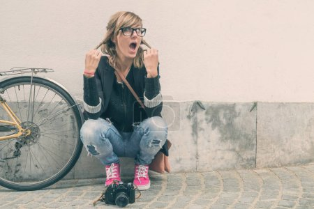 Girl with a bicycle and retro camera posing on the street.