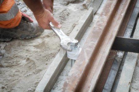 Construction worker using wrench tool to tighten the bih screw.