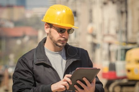 Photo for Builder with digital tablet posing on a heavy construction site. - Royalty Free Image