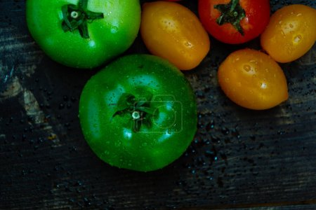 Photo for Still life with fresh red, green and yellow tomatoes freshly picked from the garden on the wooden table and kitchen knife - Royalty Free Image
