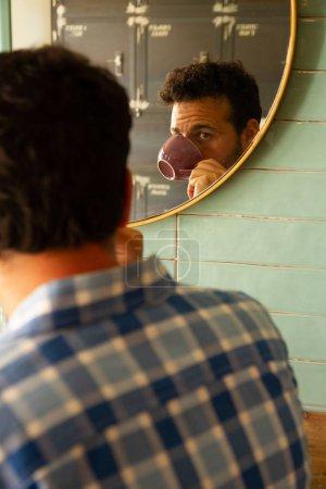 Photo pour Verticale d'un jeune homme buvant le café reflété dans un miroir - image libre de droit