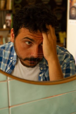 Photo pour Jeune homme touchant son cheveu regardant dans le miroir - image libre de droit