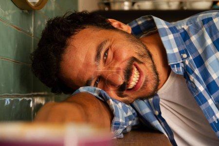 Photo pour Jeune homme se penchant sur une table de café souriant - image libre de droit